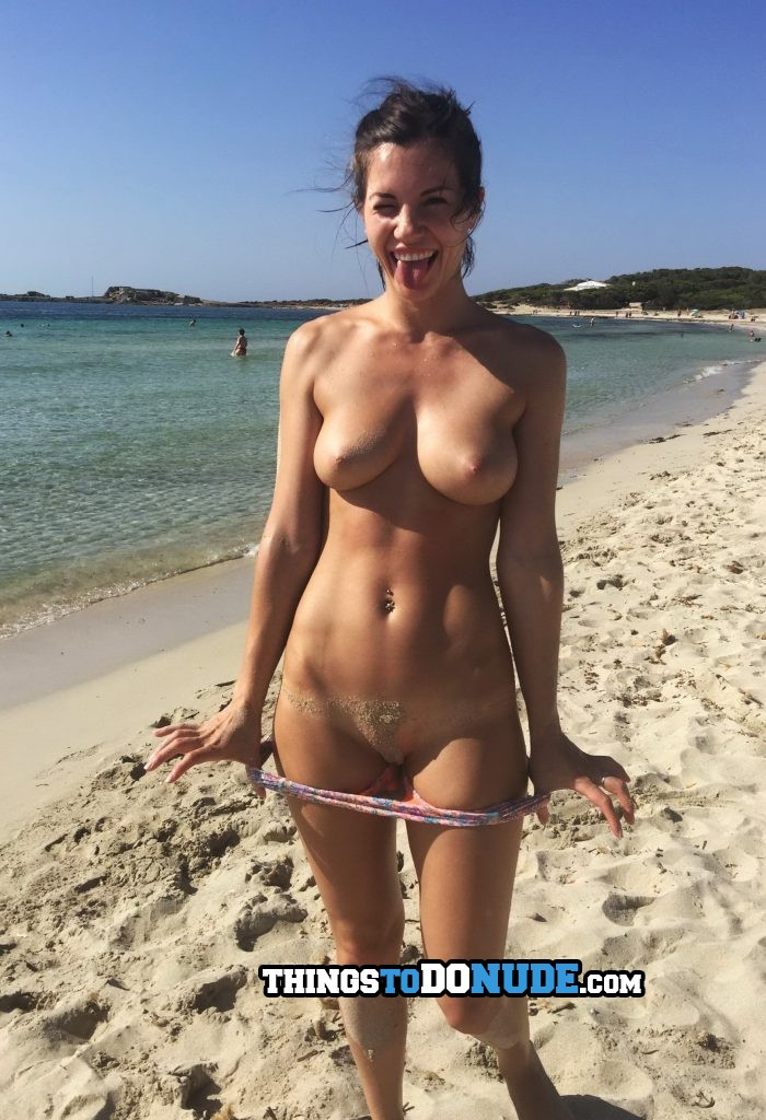 Gorgeous girl smiles while she gets naked on beach