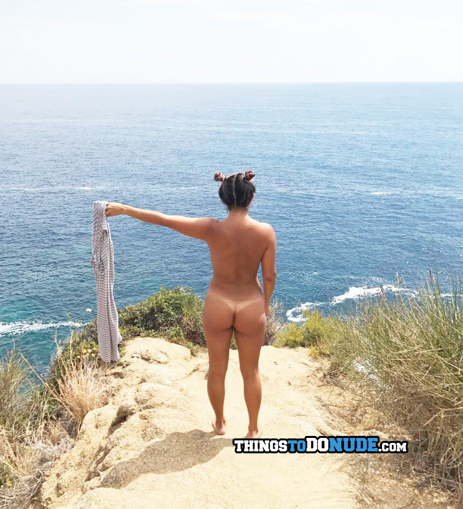 Girl undressing on the cliff overlooking the ocean