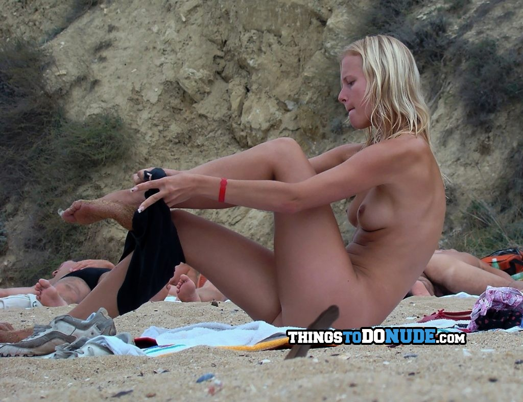 Voyeur checks out nudist girl while she gets dressed in clothes on beach
