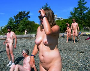Nudist woman standing on beach among other nudists