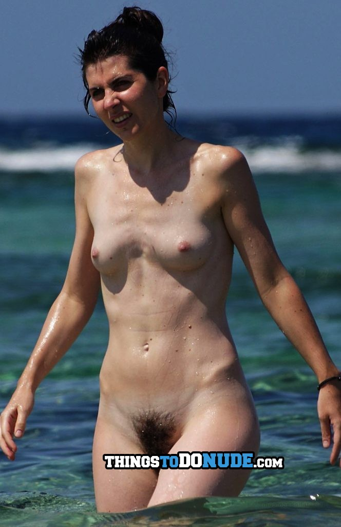 Nudist woman with hairy pussy is walking in shallow water