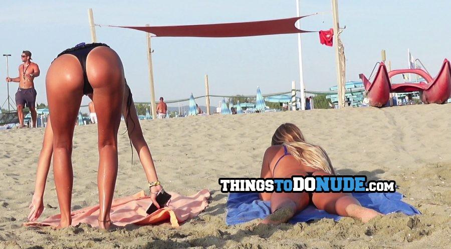 Tanned ass of hot bent over brunette teen at the beach